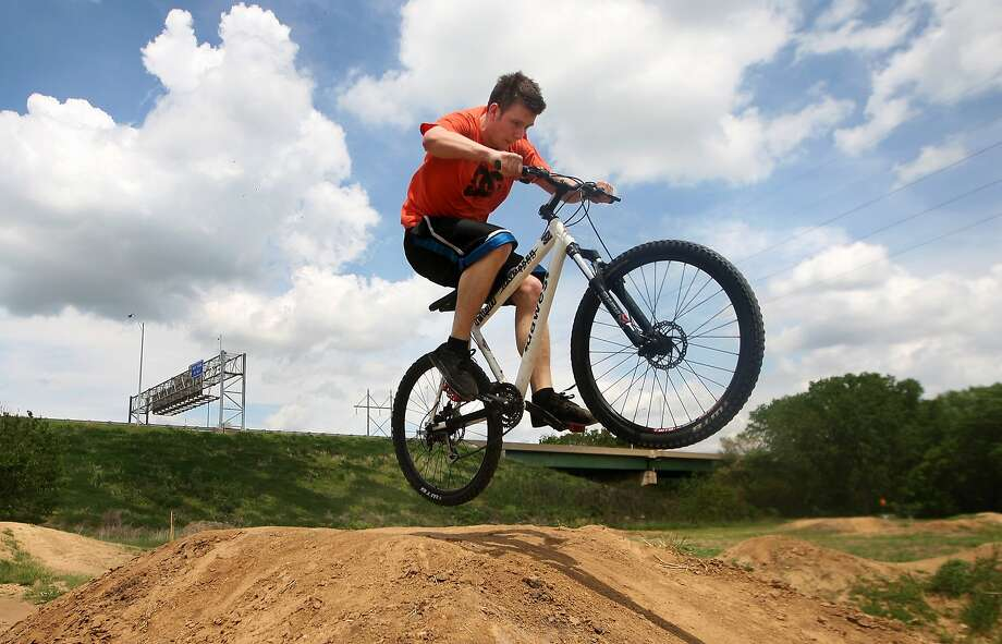 No helmet? Paris Dreibelbis catches air on one of the jumps at the Dubuque Bike Park in Dubuque, Iowa. Photo: Nicki Kohl, Associated Press