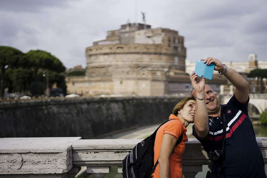 When in Rome, make a spectacle of yourself:Tourists snap a selfie in front of Rome's Castel Sant'Angelo. Photo: Domenico Stinellis, Associated Press