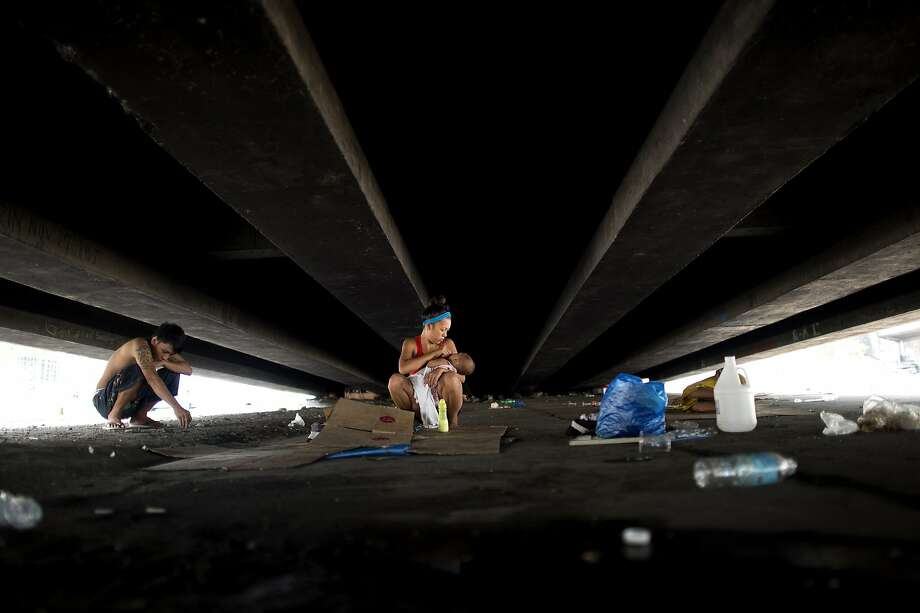 Home is under the overpass:Homeless and jobless, Filipino Richard Alcantara squats near his wife, Joana, 18, holding their daughter, under a highway in Manila. Photo: Noel Celis, AFP/Getty Images