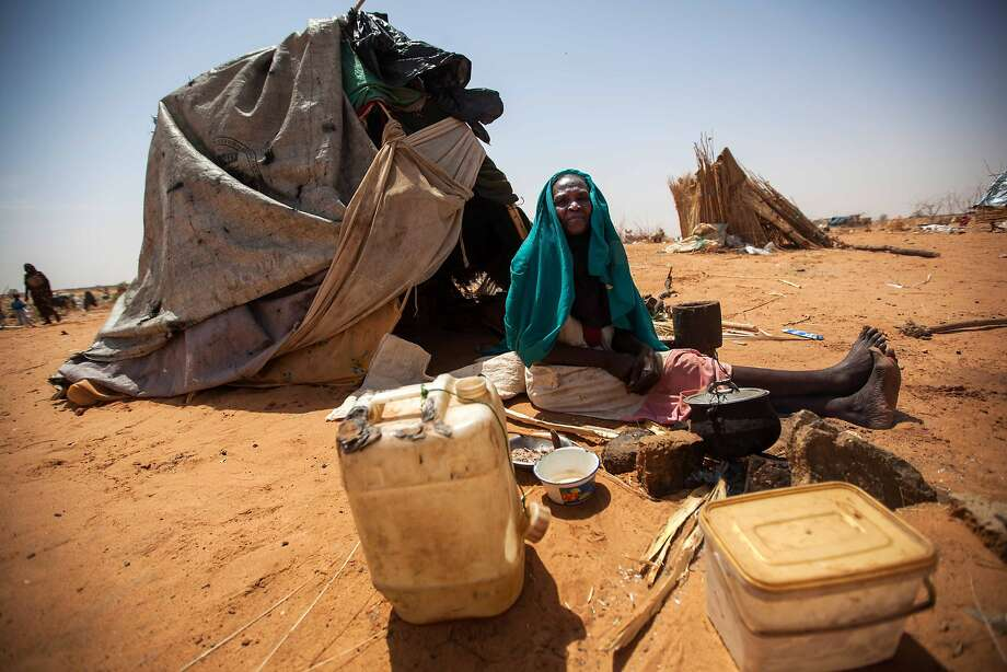 In case you've forgotten about Darfur ... Aisha Abdala, a displaced woman from Katila, South Darfur, cooks next to her makeshift shelter and few possessions at the al-Sereif 