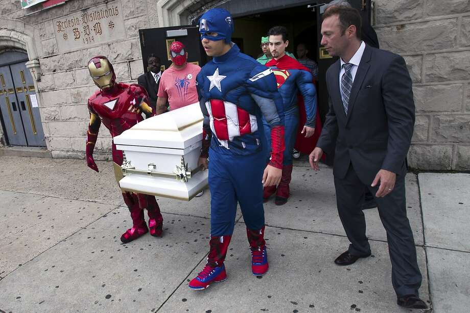 Pallbearers dressed as 7-year-old Sebastian Gerena's favorite superheroes carry his casket during his funeral in Philadelphia. The pallbearers are relatives, friends and staff at Families Forward, the West Philadelphia 