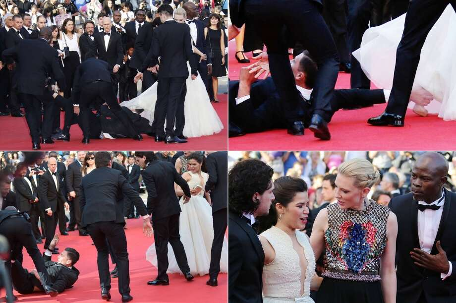"""A combination of pictures made on May 17, 2014 shows prankster Vitalii Sediuk blocked by minders as he tries to slip under US actress America Ferrera's dress as she arrives for the screening of the animated film """"How to train your Dragon 2"""" at the 67th edition of the Cannes Film Festival in Cannes, southern France, on May 16, 2014. Photo: AFP, AFP/Getty Images"""