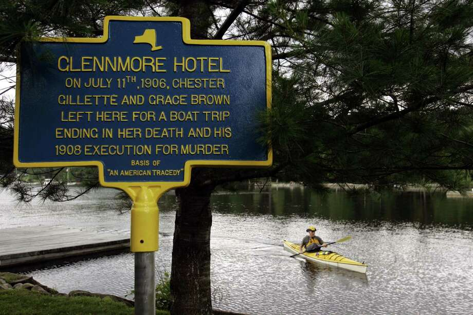 Doug Ralston, who is from Cleveland and owns a camp on Big Moose Lake, paddles to the shore where  a plaque telling about  Grace Brown  was unveiled on Tuesday, July 11, in Big Moose, Lake,  N.Y., commemorating the centennial of the murder of Grace Brown by Chester Gillette.  (AP Photo/ Jim McKnight) Photo: JIM MCKNIGHT / AP