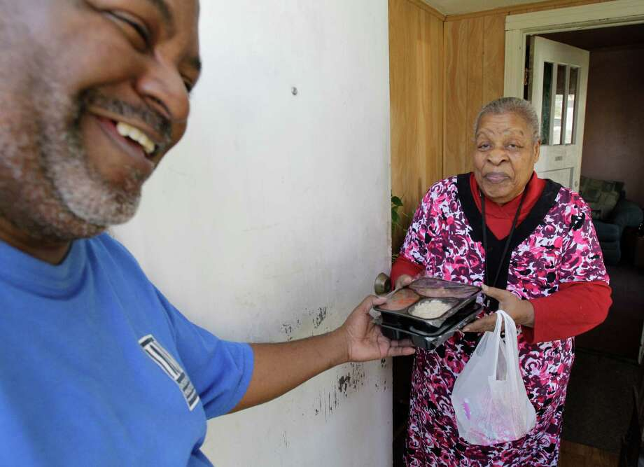 Henry Hammond, Interfaith Ministries Meals on Wheels program coordinator, delivers meals to Betty Carter for her and her sister Tuesday, March 12, 2013, in Houston. ( Melissa Phillip / Houston Chronicle ) Photo: Melissa Phillip, Staff / © 2013  Houston Chronicle
