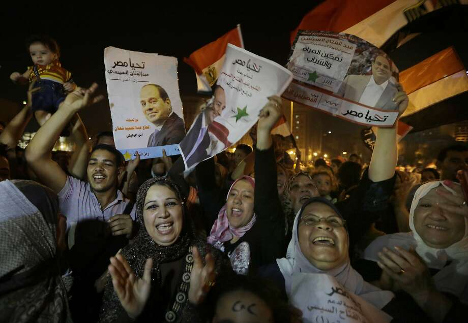 Supporters of presidential hopeful Abdel-Fattah el-Sissi, Egypt's former military chief, hold his posters during a celebration in Cairo. He won more than 92 percent of the votes. Photo: Amr Nabil, Associated Press