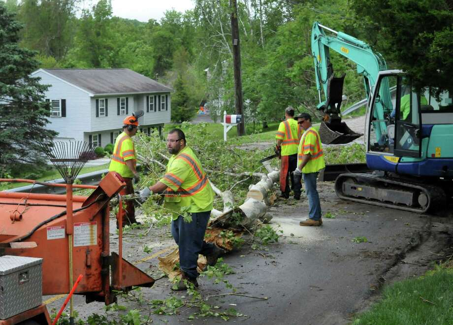 New Milford, Conn.  town workers clear debris from Van Car Road  left from a rain storm the night before, in New Milford, Conn., Wednesday, May 28, 2014. Photo: Carol Kaliff / The News-Times