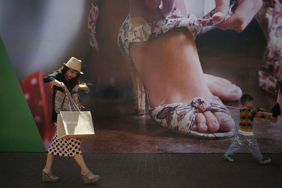 A shopper (who refused to give her name) walks past the site of a new retail development project on Market Street between 5th and 6th Streets on Thursday May 29, 2014 in San Francisco, Calif.