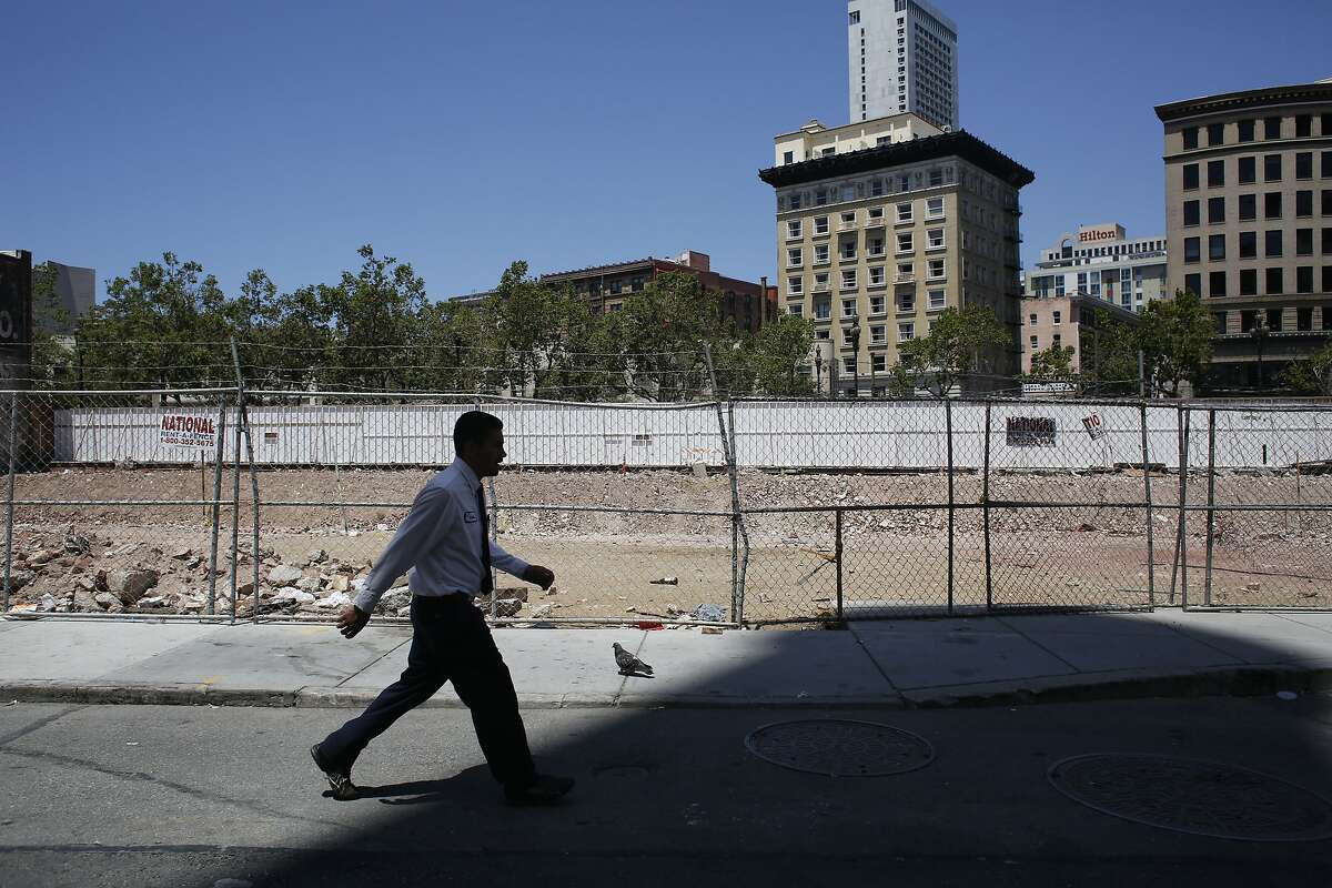 Carlos Lopez walks past the backside of a new retail development project on Market Street between 5th and 6th Streets on Thursday May 29, 2014 in San Francisco, Calif.