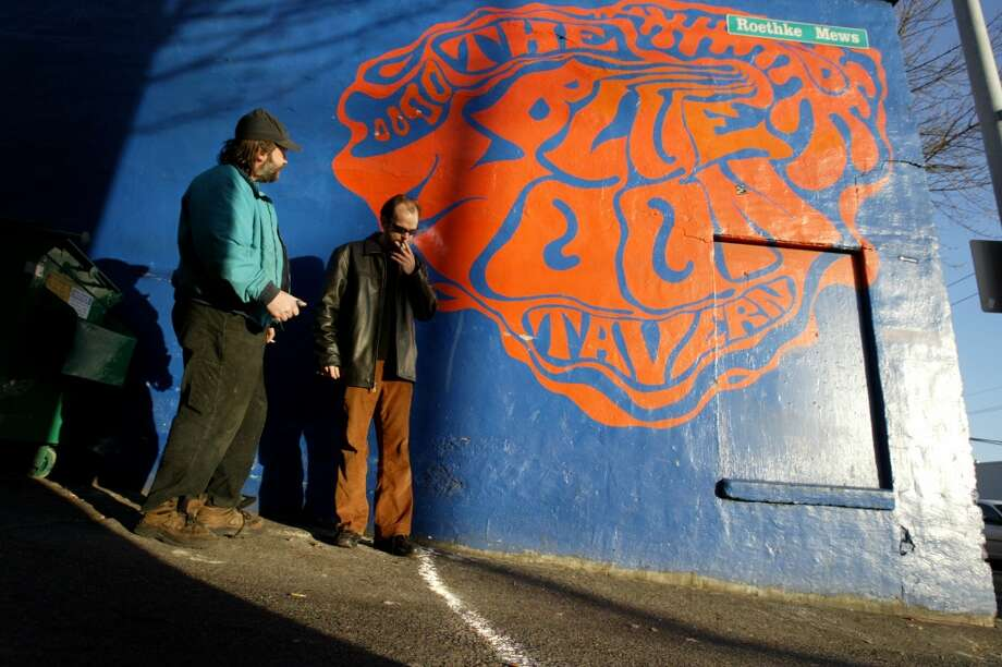 "Brandon Wald, left, and Christian Reise contemplate the white chalk line drawn around the Blue Moon  at the Blue Tavern on NE 45th Street in Seattle on December 8, 2005. The popular tavern drew a line on the sidewalk outside marking the 25 foot distance smokers must be from the front door. A bar tender was shoved to the ground when he ordered a customer to not smoke after the ban took effect, an employee said. Bar patron Duane Schneider wondered who is going to collect all the cigarette buts that are now going to litter sidewalks in front of businesses.  ""Inside the bar they collect the butts.  You can't expect businesses to set up ashtrays every 25 feet,"" he said.   Photo by Joshua Trujillo / Seattle Post-Intelligencer Photo: Joshua Trujillo, Seattle Post-Intelligencer"