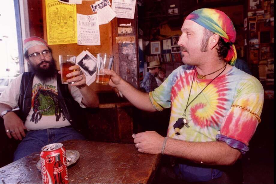 "Howard Donaghy, 43 (foreground) and Jay Delistovic, 35,  toast a beer at Seattle's Blue Moon Tavern in the University  District in honor of Grateful Dead lead singer Jerry Garcia the day of his death in 1995.  Delistovic said , ""There are a lot of bummed out Dead Heads in  here tonight."" The tavern had been packed most of the day and the  Dead music was non-stop. Photo: JEFF LARSEN, Seattlepi.com File Photo"