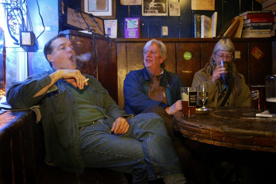 Blue Moon owner Gus Hellthaler blows smoke rings as he visits with patrons Jack Oram and Becky McPherson at the tavern in Seattle, Wash., Wednesday, Nov. 23, 2005. Photo: Seattle Post-Intelligencer
