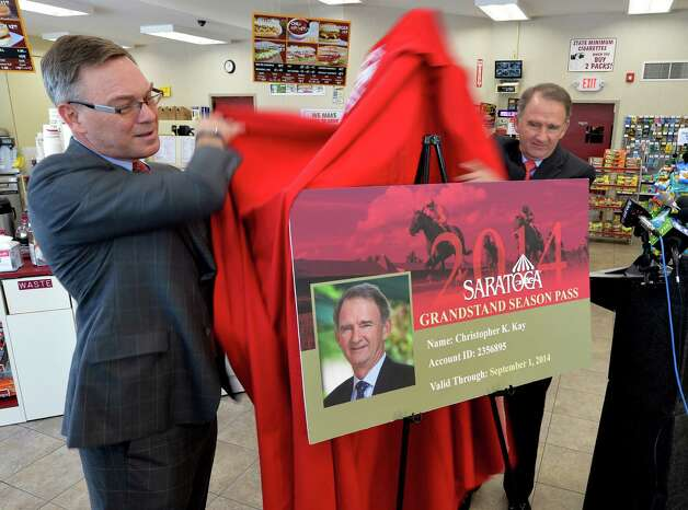 Gary Dake, president of Stewart's Shops, left and Chris Kay, CEO of the New York Racing Association, right, unveil a new discounted pass Thursday afternoon May 29, 2014,  that can be purchased at the Stewart's Shops for admission to the Clubhouse and Grandstand of the Saratoga Race Course this summer. Photo: SKIP DICKSTEIN / 00027083A
