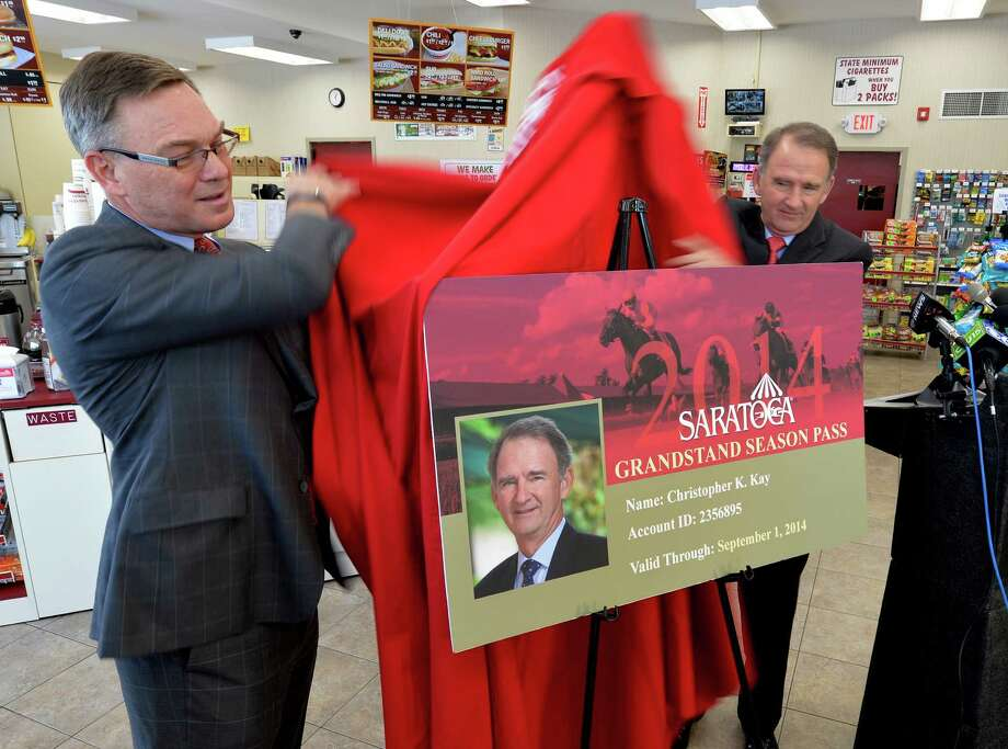 Gary Dake, president of Stewart's Shops, left and Chris Kay, CEO of the New York Racing Association, right, unveil a new discounted pass Thursday afternoon May 29, 2014,  that can be purchased at the Stewart's Shops for admission to the Clubhouse and Grandstand of the Saratoga Race Course during the meeting which begins July 18th and runs through Labor Day.  (Skip Dickstein / Times Union) Photo: SKIP DICKSTEIN / 00027083A