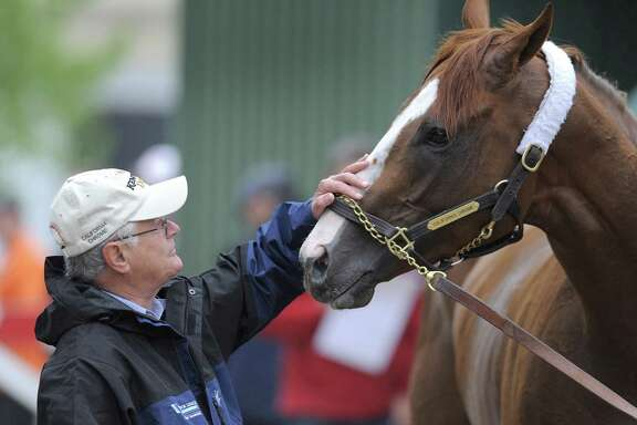Trainer Art Sherman, petting California Chrome prior to the Preakness in May, misses the horse while it races overseas.