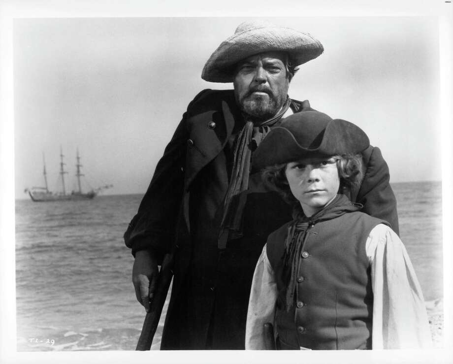 Orson Welles and Kim Burfield stand near ocean in a scene from the film 'Treasure Island', 1972. Photo: Michael Ochs Archives, Getty / 2011 Getty Images