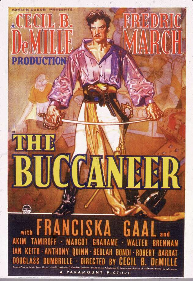 Promotional poster for the adventure film 'The Buccaneer,' directed by Cecil B. DeMille and released in 1938. Fredric March, as Jean Lafitte, dressed in a pirate's uniform, holds a sword between his outstretched arms. Photo: Hulton Archive, Getty / 2005 Getty Images