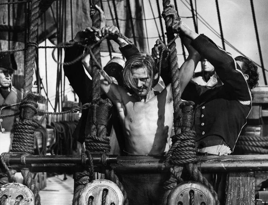 A scene from the film 'Captain Horatio Hornblower' (1951), based on the novel by C.S. Forester and directed by Raoul Walsh for Warner Brothers. A defiant Peter Morton is about to be flogged, while actors Robert Beatty and Gregory Peck look on. Original Publication: Picture Post, Nelson's Navy Unlearns English - pub. 1950 Photo: Picture Post, Getty / Moviepix