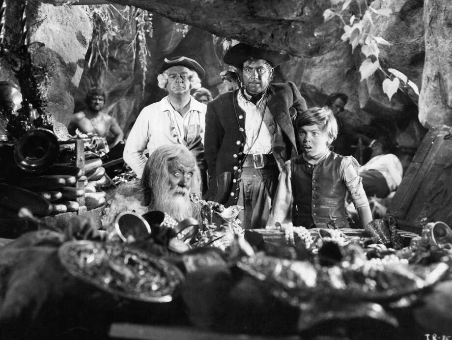 Robert Newton and Bobby Driscoll have shocked faces at the site of the old man covered in treasure in a scene for the film 'Treasure Island', 1950. Photo: Archive Photos, Getty / 2012 Getty Images