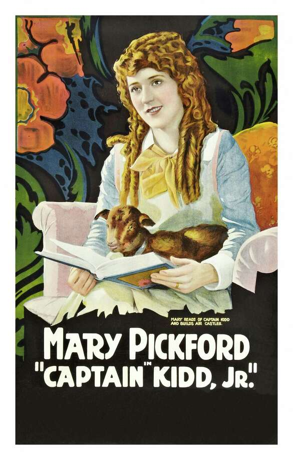 Mary Pickford holds a lamb as she reads a book on a poster that advertises the movie 'Captain Kidd Jr.,' 1919. Photo: Buyenlarge, Getty / Moviepix