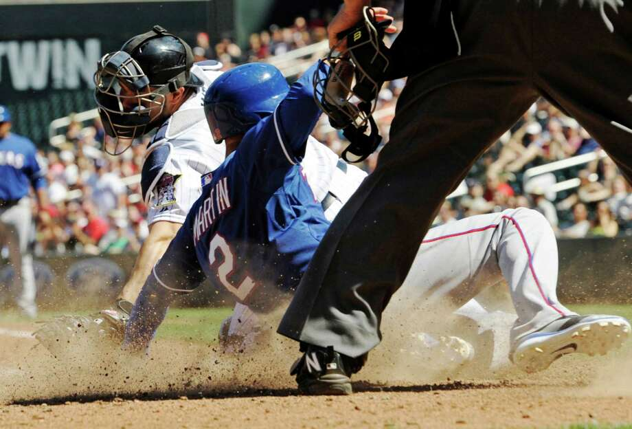 Texas Rangers' Leonys Martin, right, beats the tag by Minnesota Twins catcher Josmil Pinto to score the go-ahead run on a sacrifice fly by Rougned Odor in the eighth inning of a baseball game Thursday, May 29, 2014, in Minneapolis. The Rangers won 5-4. (AP Photo/Jim Mone) Photo: Jim Mone, Associated Press / AP