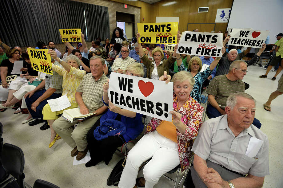 Members of the audience hold up signs before Thursday's Beaumont Independent School District's meeting. The board addressed spending and employees during the session.