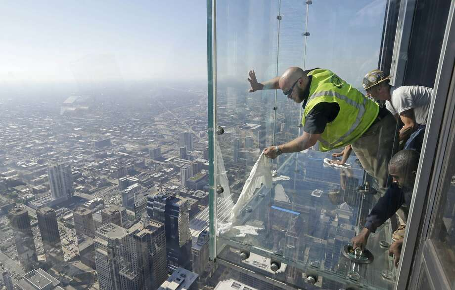 Glaziers from MTH Industries finish replacing a layer of protective coating over the glass surface on the floor of one of four transparent ledges that jut out from the 103rd floor of the Willis Tower in Chicago on Thursday, May 29, 2014. The see-through glass bays known as The Ledge were designed with a protective coating that completely covers all glass surfaces to protect against scratches. One of the coatings cracked Wednesday night when a family was standing on it. Officials say the family wasn't in danger and the coating does not affect the structural integrity of the enclosure. (AP Photo/M. Spencer Green) Photo: M. Spencer Green, Associated Press