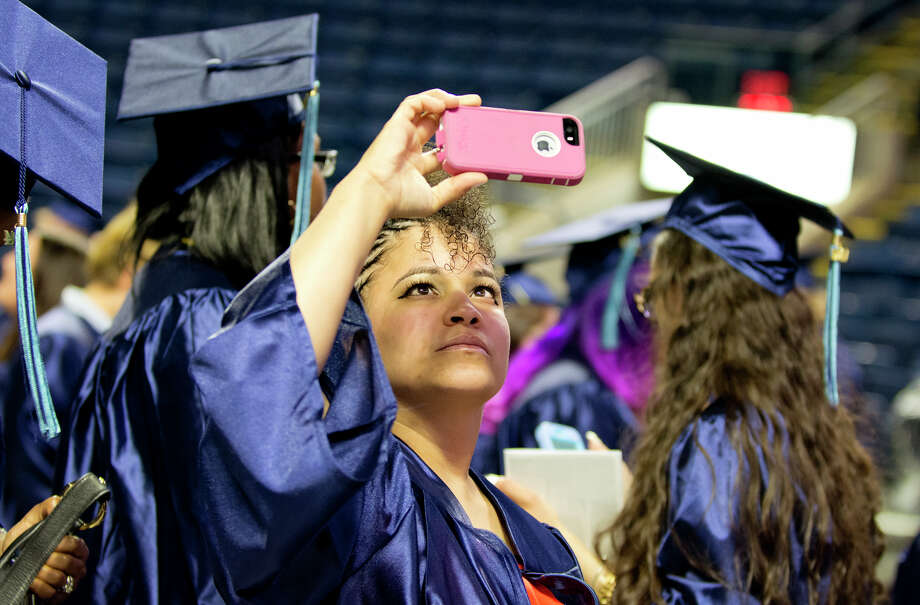 Graduate Xiomara Lugo, of Bridgeport, takes a panoramic photo during Housatonic Community College's 47th commencement at Webster Bank Arena in Bridgeport on May 29, 2014. Photo: Amy Mortensen / Connecticut Post Freelance