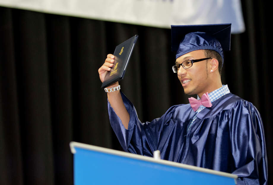 Graduate Jency Gonzalez holds up his diploma during Housatonic Community College's 47th commencement at Webster Bank Arena in Bridgeport on May 29, 2014. Photo: Amy Mortensen / Connecticut Post Freelance