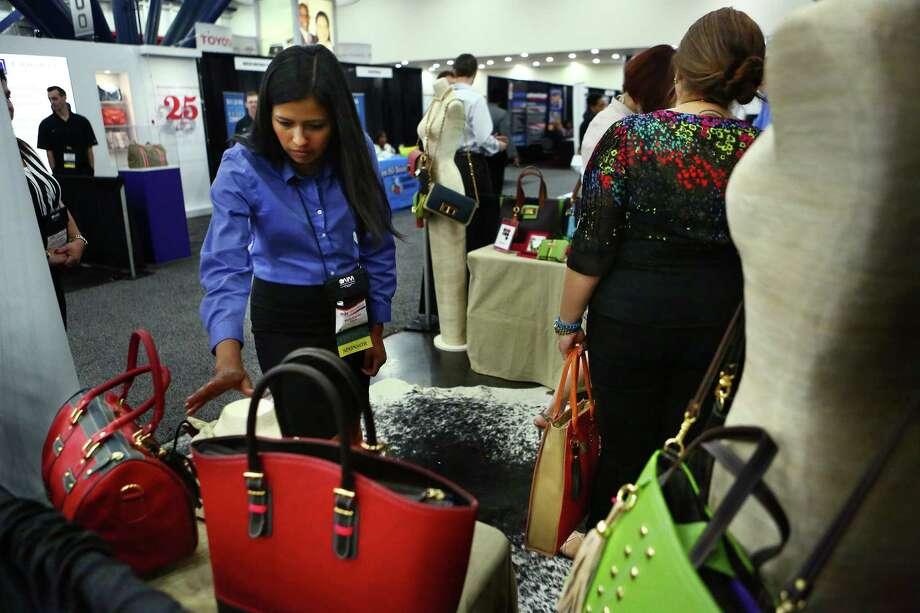 Maria Fuentes checks the ClaudiaG items at the Women's Business Enterprise Alliance Business Expo. Photo: Marie D. De Jesus, Staff / © 2014 Houston Chronicle