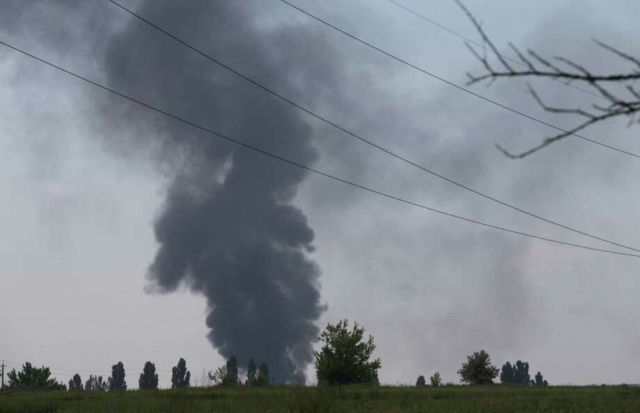 Black smoke rises from a Ukrainian army helicopter shot down by rebels with a portable air defense missile outside Slovyansk, Ukraine. Fourteen soldiers, including a general, were killed. Photo: Alexander Zemlianichenko / Associated Press / AP