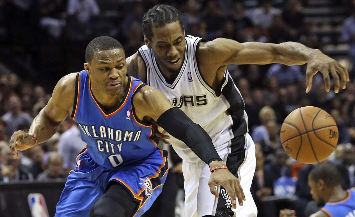 Russell Westbrook steals the ball from Kawhi Leonard after Leonard stole the ball from Kevin Durant as the Spurs play the fifth game of the Western Conference Finals against the Oklahoma City Thunder on May 29, 2014.