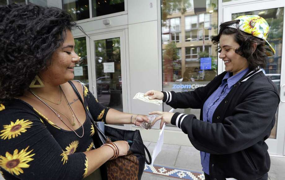 "Yeni Sleidi (right), who calls herself the ""Weed Fairy,"" buys marijuana from a dealer who declined to be identified in Seattle's Capitol Hill neighborhood this week. Photo: Associated Press / AP"