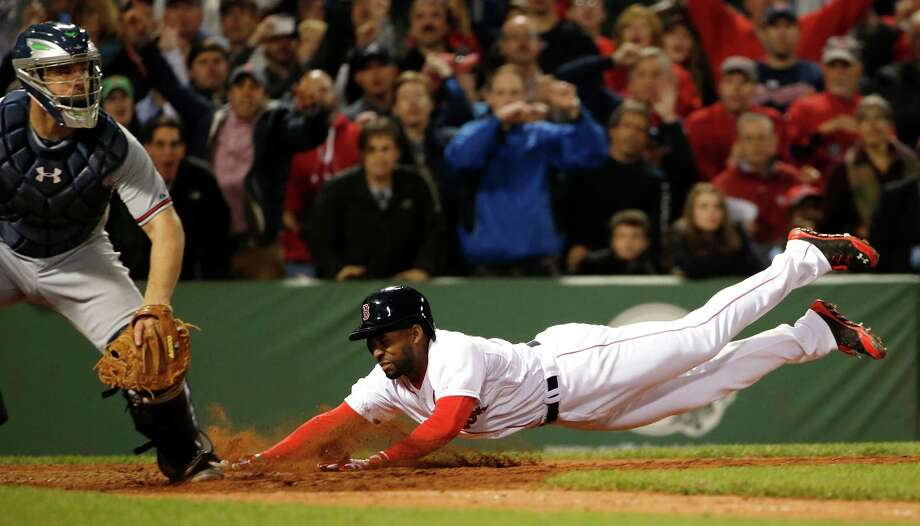 Boston Red Sox's Jackie Bradley Jr. dives home with the game-winning run on an infield single by teammate Xander Bogaerts as catcher Evan Gattis, left,  looks on during the ninth inning of their 4-3 win in a baseball game at Fenway Park, Thursday, May 29, 2014, in Boston. (AP Photo/Winslow Townson) ORG XMIT: BXF119 Photo: Winslow Townson / FR170221 AP