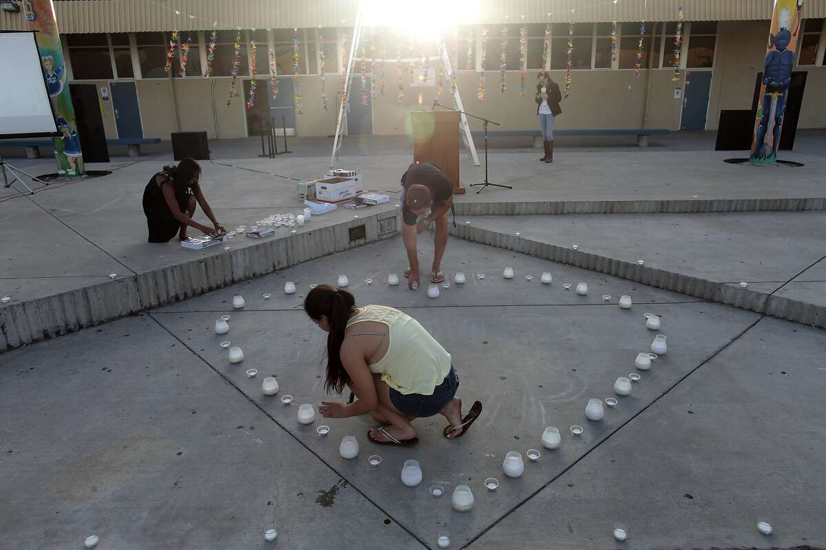 """Students set up candles for a vigil for George Chen at Leland High School in San Jose, Calif. on Thursday, May 29, 2014. George Chen was one of three Bay Area victims of the shooting in Isla Vista. Lawmakers passed AB1014 to create a """"gun violence restraining order"""" in order to keep guns away from a person threatening to harm others. The bill by Assembly members Nancy Skinner, D-Berkeley, and Das Williams, D-Santa Barbara, was drafted last year but revived earlier this year after the shooting rampage at Isla Vista near UC Santa Barbara."""