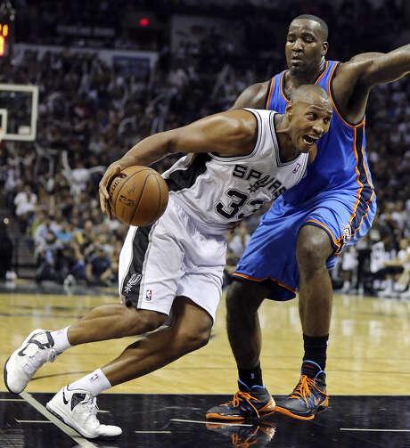 Boris Diaw of the Spurs, who had 13 points — including two 3-pointers — and six rebounds, drives around Thunder center Kendrick Perkins. Photo: Edward A. Ornelas / San Antonio Express-News / © 2014 San Antonio Express-News