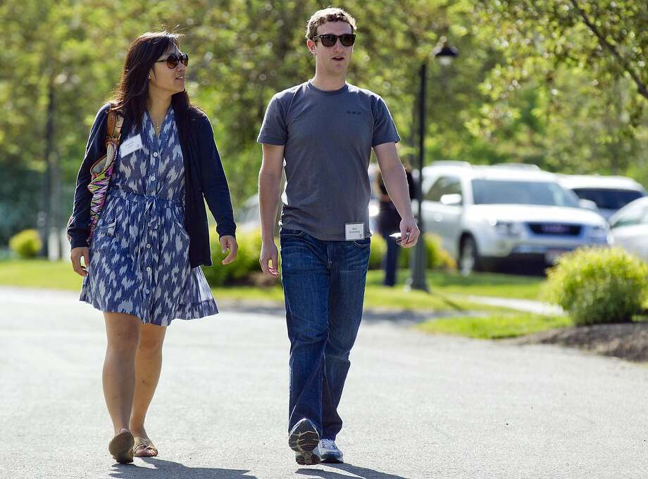 In this file photo, Mark Zuckerberg, president and CEO of Facebook, walks to morning sessions with Priscilla Chan during the 2011 Allen and Co. Sun Valley Conference, in Sun Valley, Idaho.  Zuckerberg and his wife, Priscilla Chan, are donating $120 million over 