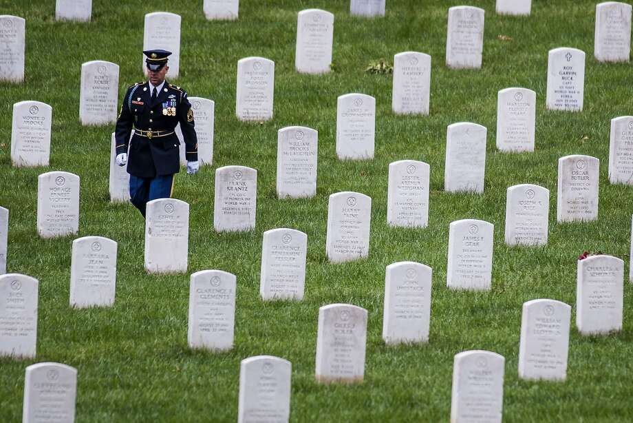 A member of the honor guard takes his position during burial services for Army Pfc. James Holmes of Warren, Ohio, missing from the Korean War, Thursday, May 29, 2014, at Arlington National Cemetery in Arlington, Va. Earlier this month, The Department of Defense POW/Missing Personnel Office (DPMO) announced that the remains of a U.S. serviceman, missing from the Korean War, had been identified as Holmes and returned to his family for burial with full military honors. (AP Photo/Kevin Wolf) Photo: Kevin Wolf, Associated Press