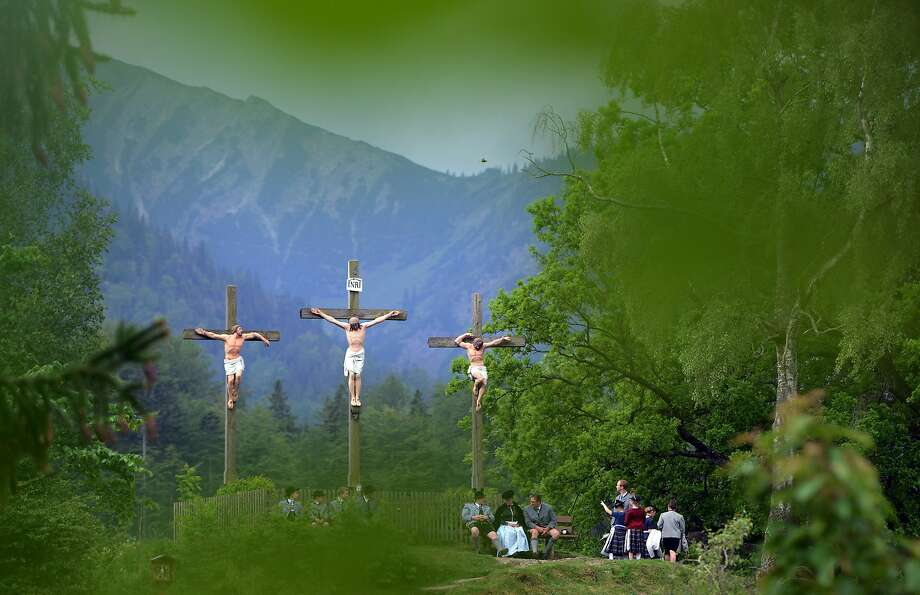 *** BESTPIX *** FISCHBACHAU, GERMANY - MAY 29:  Pilgrims in traditional Bavarian folk costumes stand beneath three crosses on the Kalvarienberg-mountain and follow an outdoor mass to celebrate Ascension (in German called Christi Himmelfahrt) at the open-air altar at Birkenstein on May 29, 2014 near Fischbachau, Germany. Approximately 2,000 pilgrims from 40 different folk group associations participated in the annual event to mark Jesus Christ's ascension to Heaven. Bavaria is predominantly Catholic.  (Photo by Joerg Koch/Getty Images) Photo: Joerg Koch, Getty Images
