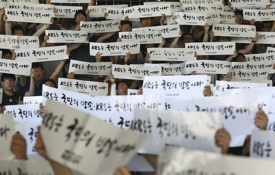 "Union members of the KBS, Korea Broadcasting System, hold up their banners during a rally against the government at the KBS headquarters in Seoul, South Korea, Thursday, May 29, 2014. They went on a strike on Thursday demanding that their President Gil Hwan-young resign for allegedly interfering in news reporting in favor of the government. The writing reads: ""The KBS is a public broadcasting."" (AP Photo/Ahn Young-joon) Photo: Ahn Young-joon, Associated Press"