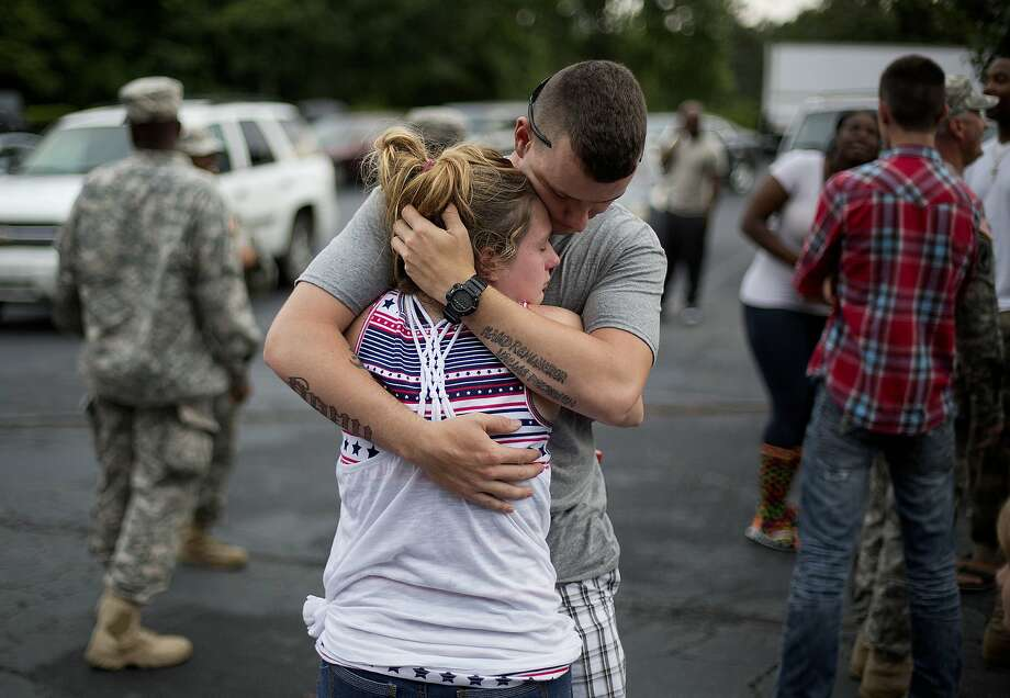 Spc. Wesley Freeman, right, embraces his girlfriend Christie McCarron as he says goodbye before roll call on the eve his unit, the Georgia National Guard 876th Vertical EN Company, deploys to Afghanistan, Thursday, May 29, 2014, in Toccoa, Ga. This is Freeman's second deployment only having returned from his first in November of 2013. The unit's deployment marks the last for the Georgia Army National Guard to Afghanistan as the military looks to withdrawal all but some 10,000 troops after 2014. Officials say the work of the nearly 150 guardsmen overseas will include repair, construction, plumbing and more. (AP Photo/David Goldman) Photo: David Goldman, Associated Press