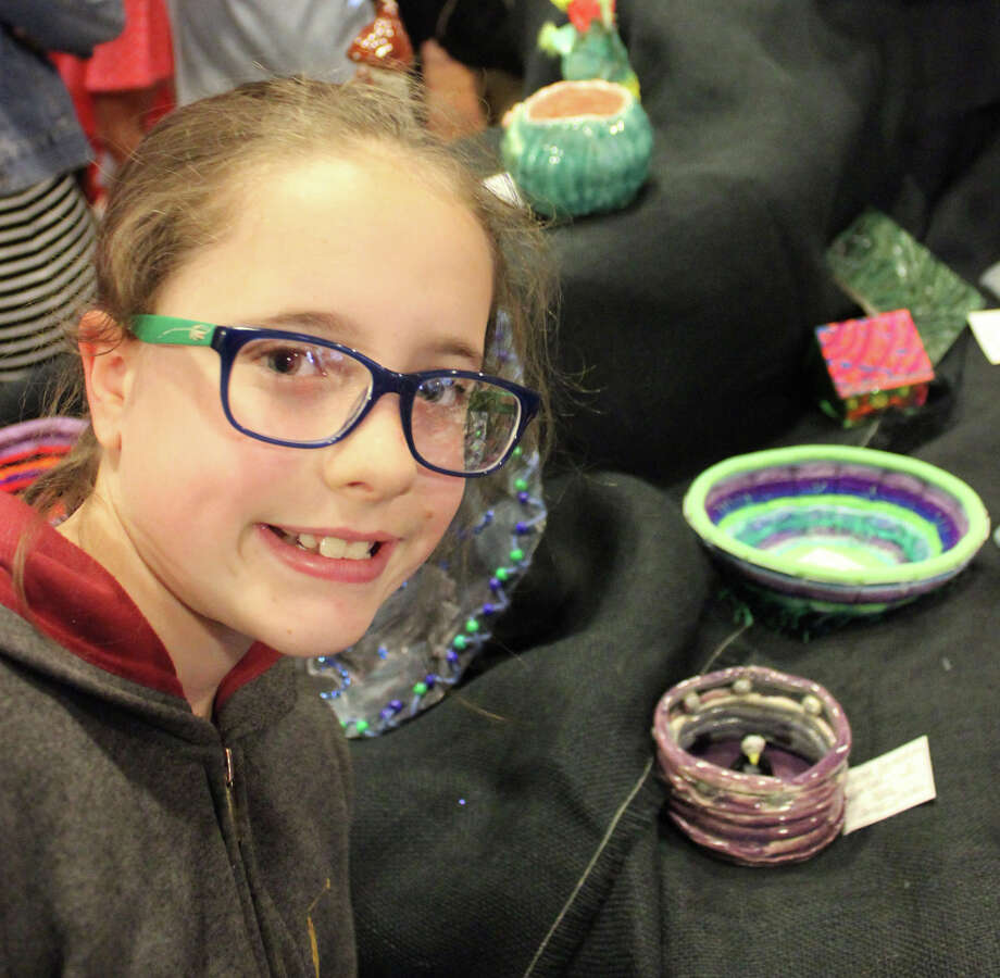 "Rachel Bernaschina, who is in the fifth grade at Riverfield Elementary School, shows off her ""Purple Penguin"" pottery piece at the 40th annual Townwide Student Art Show, hosted by the Pequot Library. Photo: Contributed Photo /  Fairfield Citizen contributed"