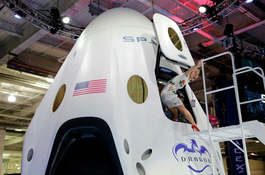 Invited guest Robin Lee walks out of the cabin of the SpaceX Dragon V2 spacecraft at the SpaceX headquarters on Thursday, May 29, 2014, in Hawthorne, Calif. SpaceX, which has flown unmanned cargo capsules to the International Space Station, unveiled the new spacecraft Thursday designed to ferry up to seven astronauts to low-Earth orbit. Photo: Jae C. Hong, AP / AP