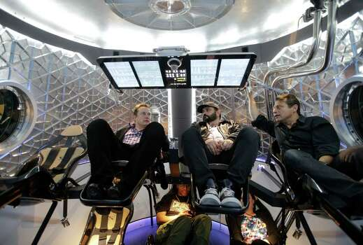 Elon Musk, left, CEO and CTO of SpaceX, mingles with invited guests inside the SpaceX Dragon V2 spaceship at the headquarters on Thursday, May 29, 2014, in Hawthorne, Calif. SpaceX, which has flown unmanned cargo capsules to the International Space Station, unveiled the new spacecraft Thursday designed to ferry astronauts to low-Earth orbit.