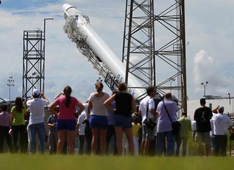 CAPE CANAVERAL, FL - OCTOBER 07:  People watch as a SpaceX Falcon 9 rocket attached to the cargo-only capsule called Dragon is raised into launch position as it is prepared for a scheduled evening launch on October 7, 2012 in Cape Canaveral, Florida. The rocket will bring cargo to the International Space Station that consists of clothing, equipment and science experiments.  (Photo by Joe Raedle/Getty Images) Photo: Getty Images