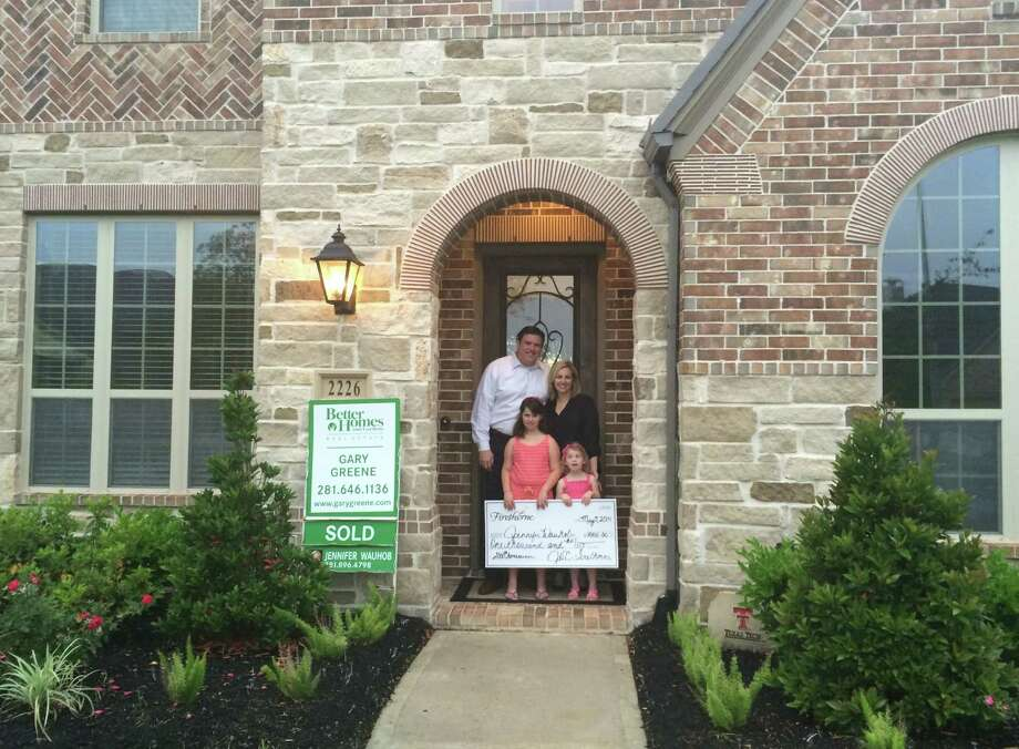 Jennifer and Todd Wauhob are the 2,000th homeowners to purchase a new home at Firethorne, a 1,400-acre master-planned community designed for 3,400 homes when completed. Firethorne's developer presented the family with a $1,000 check to celebrate this milestone for the Katy/Fulshear residential community, which the Wauhobs immediately contributed to the Firethorne Firefish swim team as platinum sponsors.  Jennifer and Todd moved to Firethorne with their daughters Ella, 8, and Ava, 3½. Ella belongs to the swim team. Photo: Firethorne