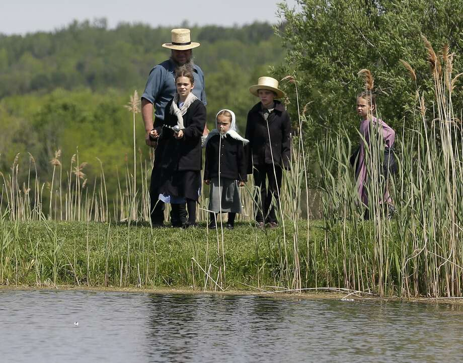 I think the bobber moved! Amish kids enjoy watching their sister fish in Fairfield, N.Y. Photo: Mike Groll, Associated Press