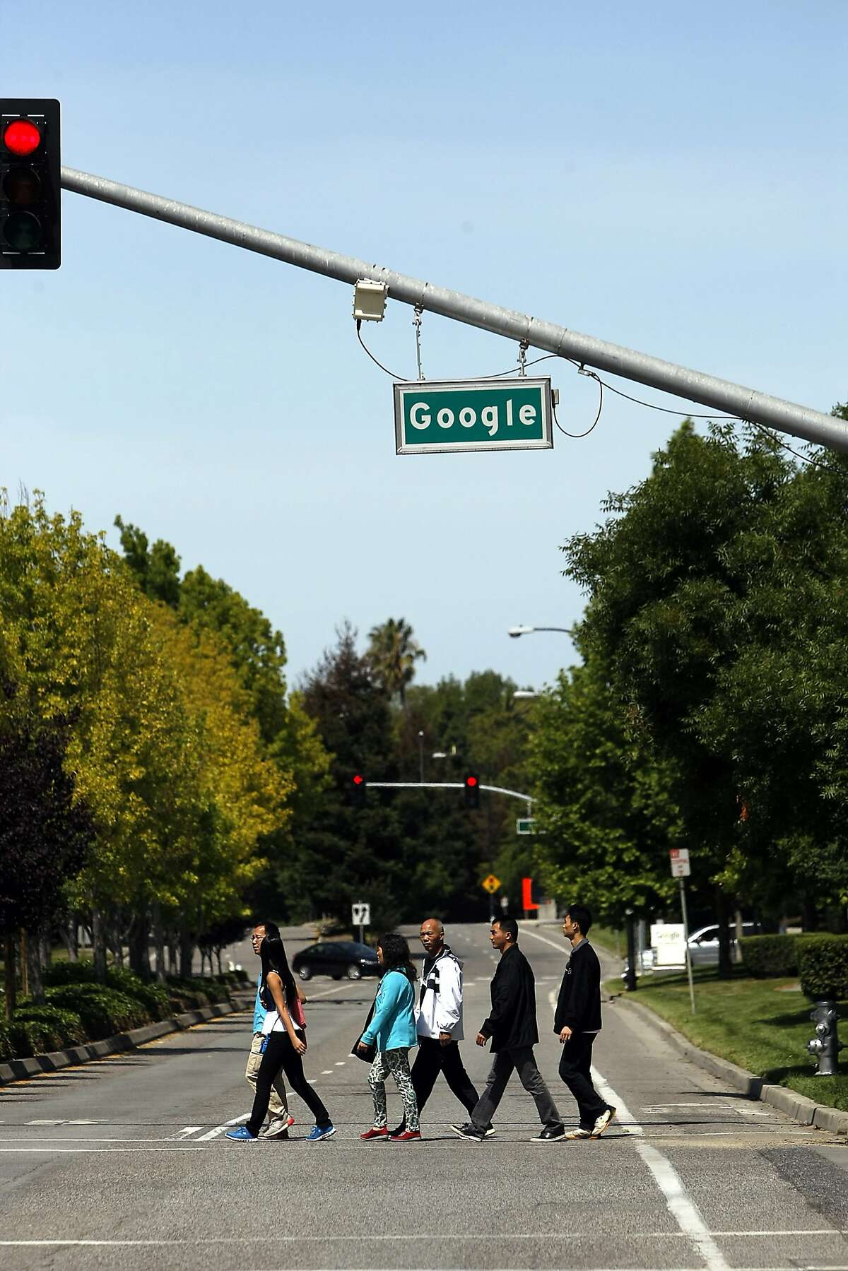 A group of tourists crosses Charleston Rd. under a Google street sign on the Googleplex campus in Mountain View, CA, Saturday May 24, 2014.