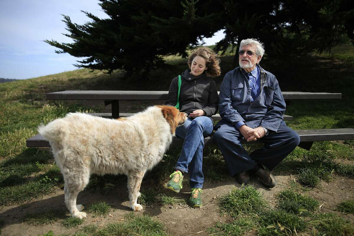 UC Berkeley Professor Richard Taruskin (right) and Nell Cloutier (left), UC Berkeley PhD candidate, talk on a bench as Cloutier greets a passing dog out for a walk at Point Isabel before Taruskin and Cloutier head out for a walk on Friday, May 16, 2014 in Richmond, Calif.