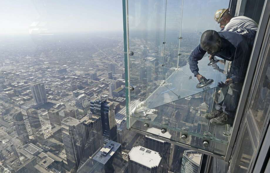 Perfectly safe:Glaziers replace a layer of protective coating over the glass surface on   the floor of one of four transparent ledges that jut out from the 103rd floor of the Willis Tower in   Chicago. The see-through glass bays were designed with a protective   coating that completely covers all glass surfaces to protect against scratches. One of the coatings   cracked Wednesday evening when a family was standing on it, but officials said they were in no danger as the coating does not affect the structural integrity of the enclosure. Photo: M. Spencer Green, Associated Press