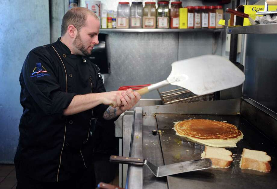 Executive chef Joseph Mastersanti makes his signature pancake at The Pantry, a new breakfast and lunch restaurant in downtown Ansonia, Conn. Mastersanti uses a pizza peel to flip his pancakes because of their size. Photo: Autumn Driscoll / Connecticut Post